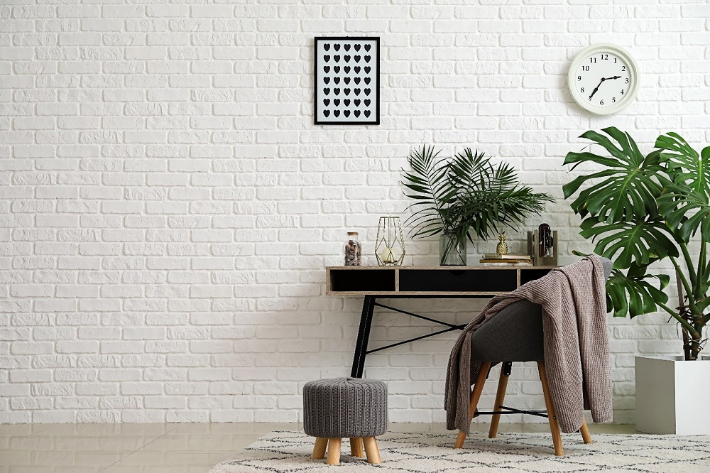 Decorate a room with indoor plants, ottoman foot stool, a chair and a desk