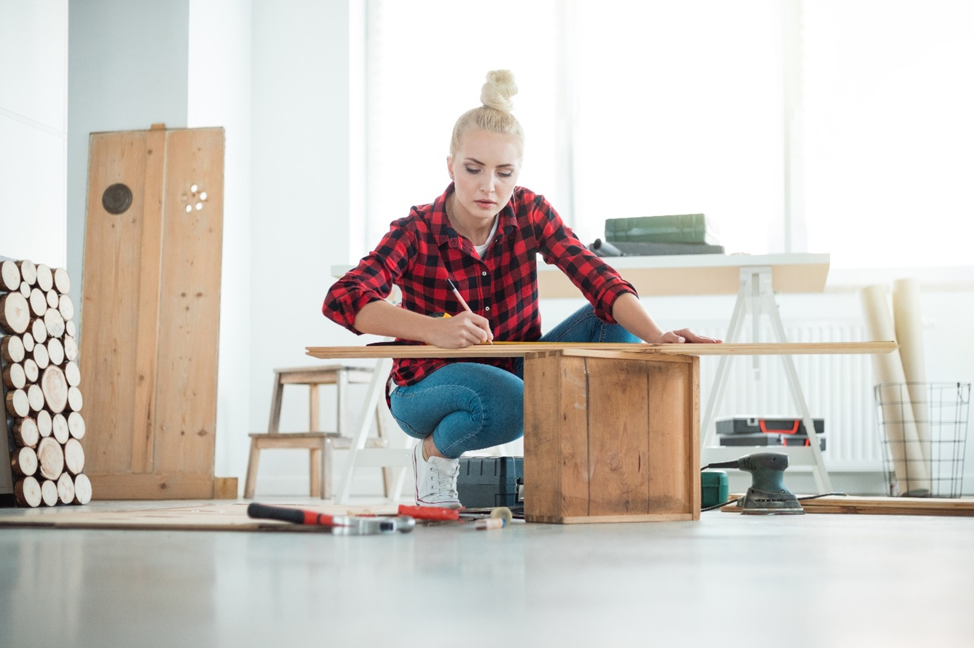 A Woman Measuring Wooden Board For Her Furniture